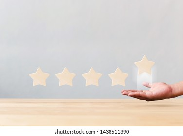 Hand holding wooden five star shape on table. The best excellent business services rating customer experience concept
