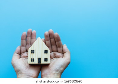 Hand holding wooden house model on blue background for self-quarantine and staying home in coronavirus or Covid-2019 situation concept