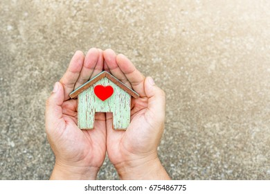 Hand holding a wooden house model in garden, Financial planning to buy a first home for the family concept.