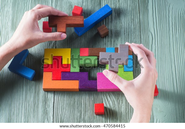 Hand holding wooden puzzle element. Hand sets the last element of the puzzle. The concept of logical thinking. Geometric shapes on a wooden background. Tetris toy wooden blocks.