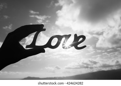Hand holding up the word love.