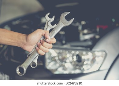 Hand holding wrench.  Auto repair shop service.