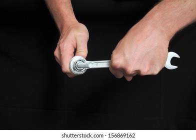An Hand Holding a Wrench over a Black Background