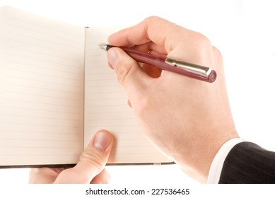 Hand holding and writing on empty notepad (notebook) isolated on white