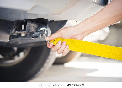 Hand holding yellow car towing strap with car, car towing