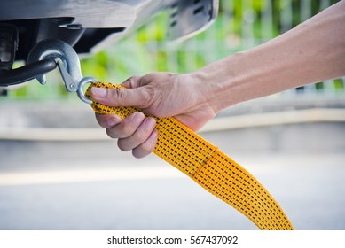 Hand holding yellow car towing strap with car, car towing, towing rope