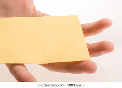 Hand holding yellow color rectangular paper on a white background