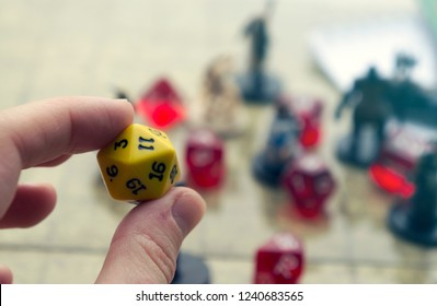 A hand holding yellow d20 dice. Rpg characters and dices on blurred background.