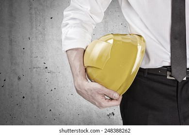 Hand holding a yellow hard hat in front of a concrete wall