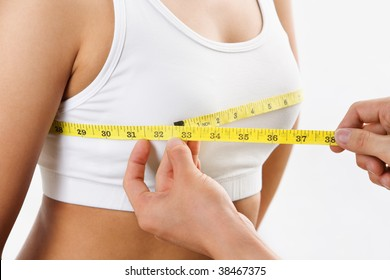 hand holding yellow measuring tape, measures bra cup size of a female body