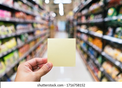 Hand holding a yellow note in blur supermarket aisle background
