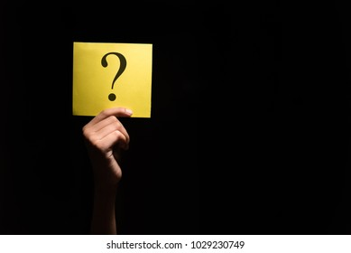 hand holding a yellow paper with question mark in a dark background