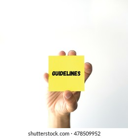 Hand holding yellow sticky note written GUIDELINES word