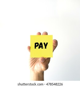 Hand holding yellow sticky note written PAY word