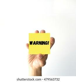 Hand holding yellow sticky note written WARNING!