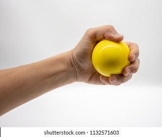 Hand holding yellow stress ball isolated on white background.