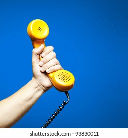 hand holding a yellow vintage telephone over a blue background