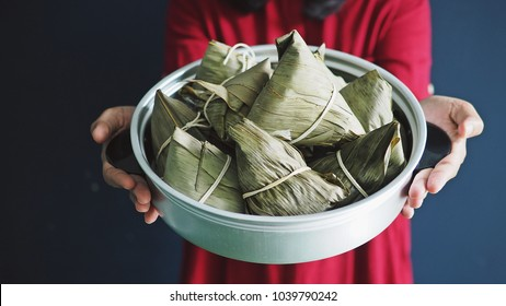 Hand holding zongzi or rice dumpling in vintage aluminium steamer or steaming pot. Zongzi is basically glutinous rice with sweet or savoury fillings wrapped in bamboo or reed leaves.