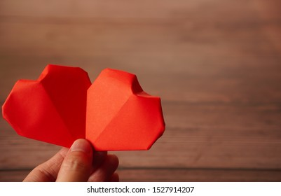 A hand holds 2 origami paper hearts on wooden background , Love ,Valentine ,Sweetest day concept with copy space