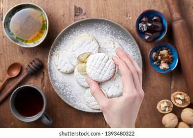 Hand holds Arabic homemade cookies filled with dates and walnuts covered powdered sugar. Eid or Ramadan festival concept. Closeup view of top