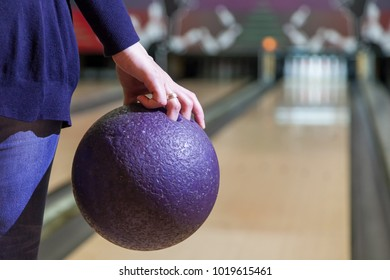 hand holds ball for bowling game before throwing, the ball for bowling game closeup