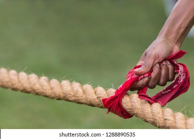A hand holds a bandana attached to a thick rope before the start of a tug of war contest.