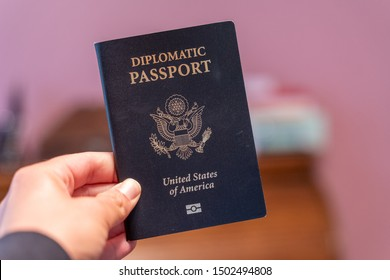 Hand holds up black Diplomatic Passport for the United States of America
