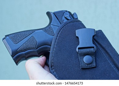 hand holds a black pistol in a holster on a gray background