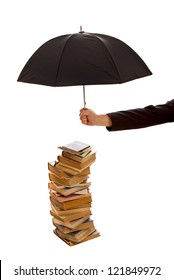 Hand holds black umbrella protecting stack of old books isolated on white