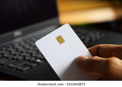 Hand holds blank smart card in front of computer