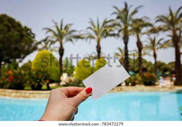 hand holds a business card on the background of the pool, palms and sky.