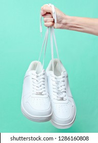 The hand holds by shoelaces hipster white sneakers on mint-colored background. Minimalism