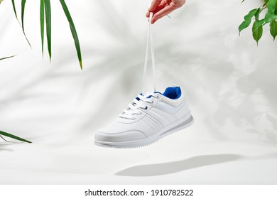 The hand holds by shoelaces white sneakers. Hand hold sporty shoes on a white background with palm leaves. Concept summer holiday.