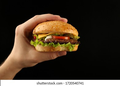 hand holds classic burger on black background with copy space