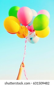 Hand holds a colorful bundle of air balloons on a blue sky background