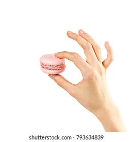 Hand holds colorful macaroons on a white background. Closeup.