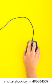 Hand holds a computer mouse. On a yellow background. Top view. Flat lay.