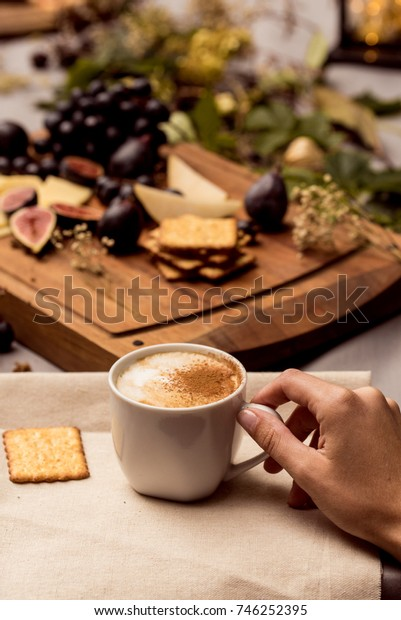 Hand holds cup of coffee with food in background
