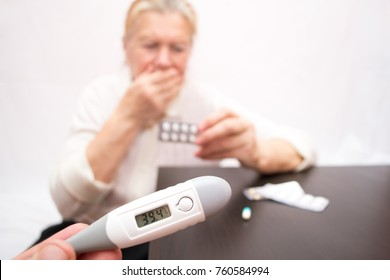 the hand holds a digital thermometer with a high temperature on the background of a coughing elderly woman and a mountain of tablets. hyperthermia due to influenza
