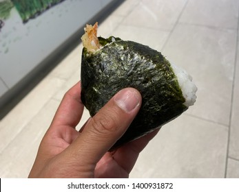 Hand holds a Ebi Onigiri, Shrimp Tempura Onigiri. Onigiri is a popular snack in Japan. It can usually be found in the deli area of Japanese grocery or convenient stores.