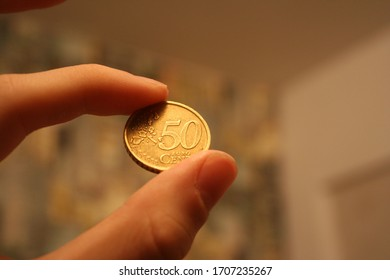 The hand holds a fifty Euro cent coin between two fingers