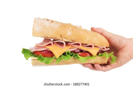 Hand holds french baguette sandwich. Isolated on a white background.