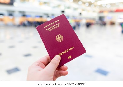 A hand holds a german passport in an airport terminal