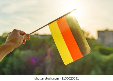 Hand holds Germany flag an open window. Background blue sky, silhouette of the city, sunset.