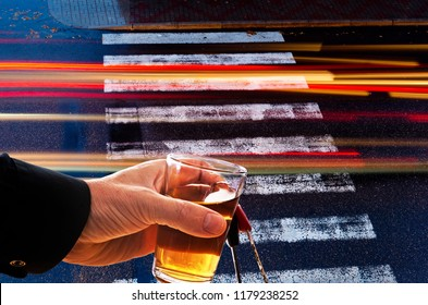 Hand holds glass of alcohol with car keys