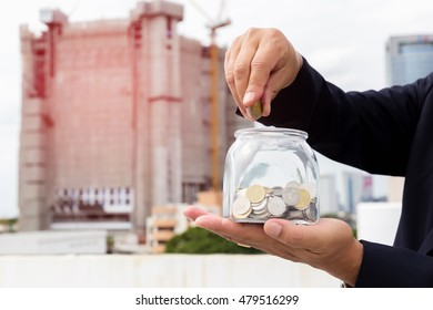 Hand holds a glass jar containing thai coins and money collect money to build a house.