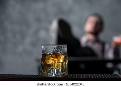 Hand holds glass with whiskey and ice and blurred man sits