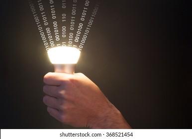 Hand holds a glowing bulb emitting data