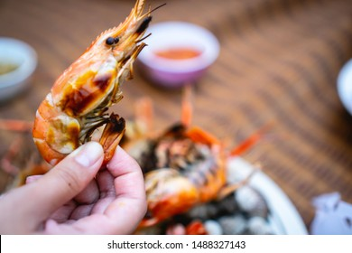 Hand holds grilled giant river prawns (giant freshwater prawns) with grilled giant river prawns and grilled cockles in the white dish background.