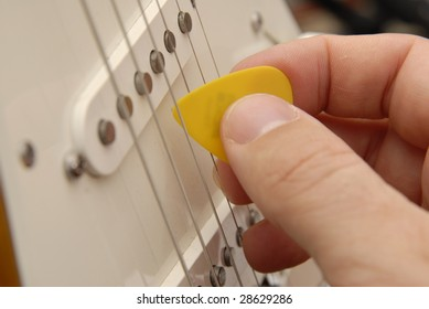 A hand holds a guitar pick and strums an electric guitar.